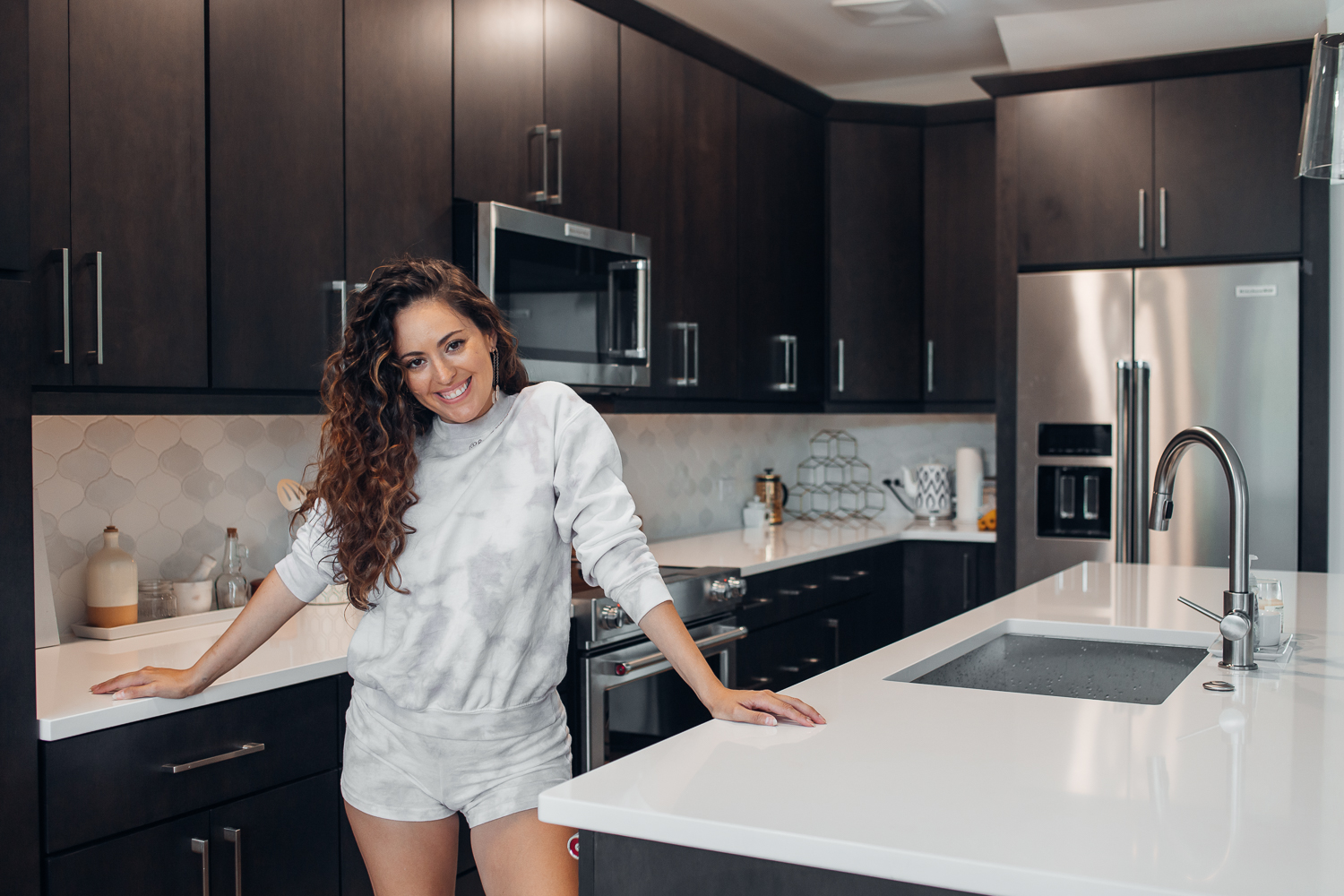 woman standing in kitchen smiling
