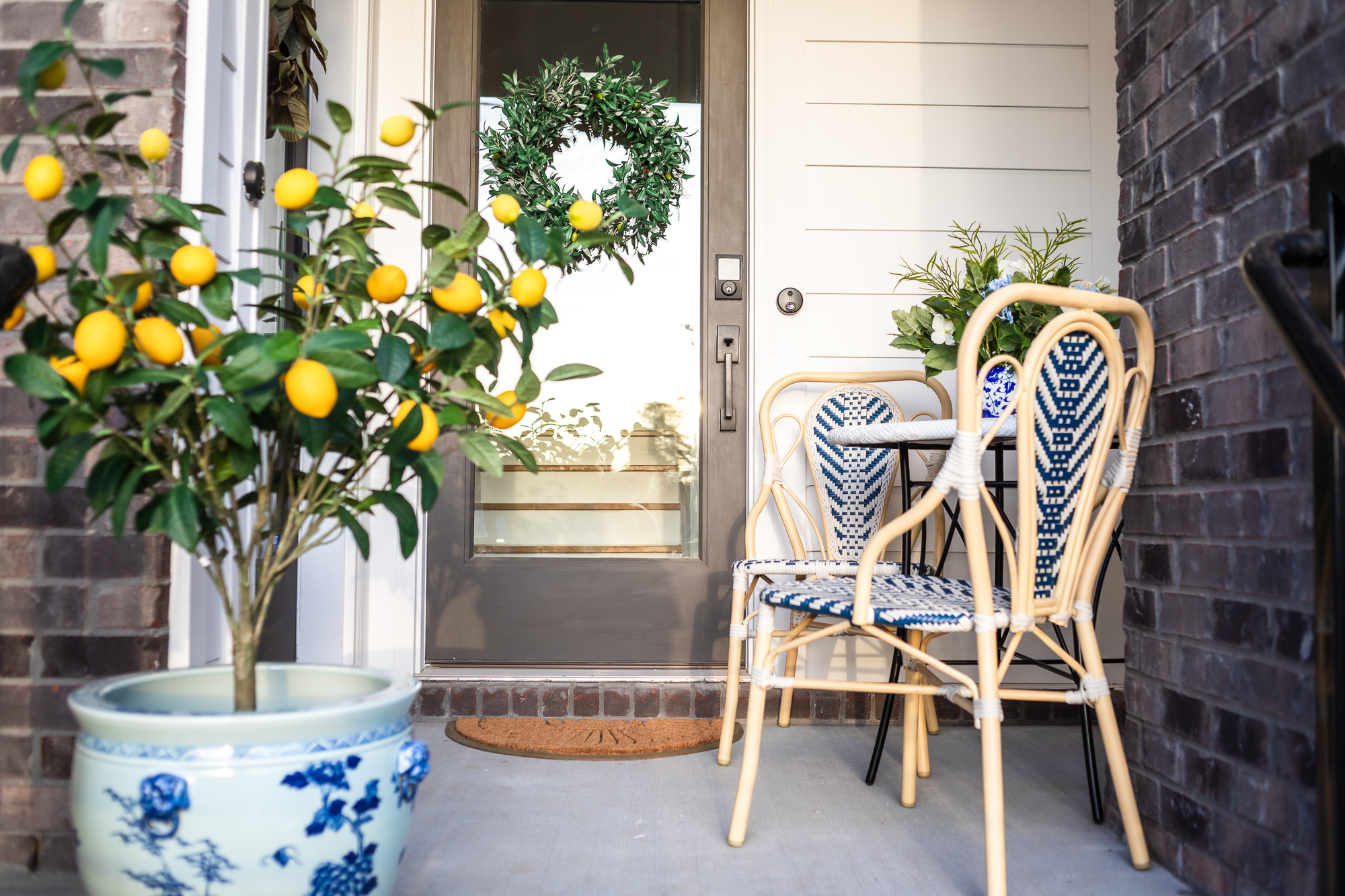 """front porch spring styling, front porch decor, how to decorate a front porch for spring, faux trees, faux plants, faux greenery, faux lemon tree, spring home decor, frontgate Keller Bistro chair set of two, frontgate menorca bistro table, frontgate Sunburst Half-round Coco Door Mat, frontgate 50"""" Outdoor Lemon Potted Tree, frontgate Blue Ming Handpainted Ceramic Planters, frontgate Lush Olive Leaf Wreath, frontgate Blooming Mixed Hydrangea in Ming Vase"""